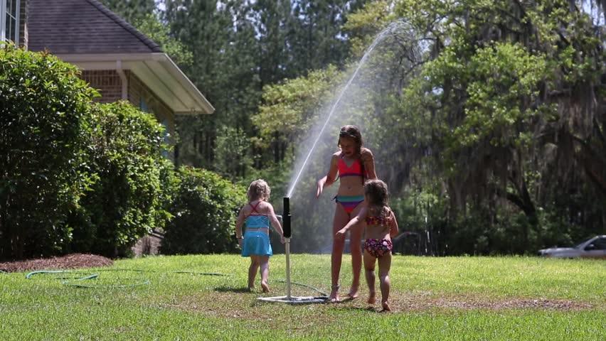 Girls playing in sprinkler   Shutterstock HD Video #13591874