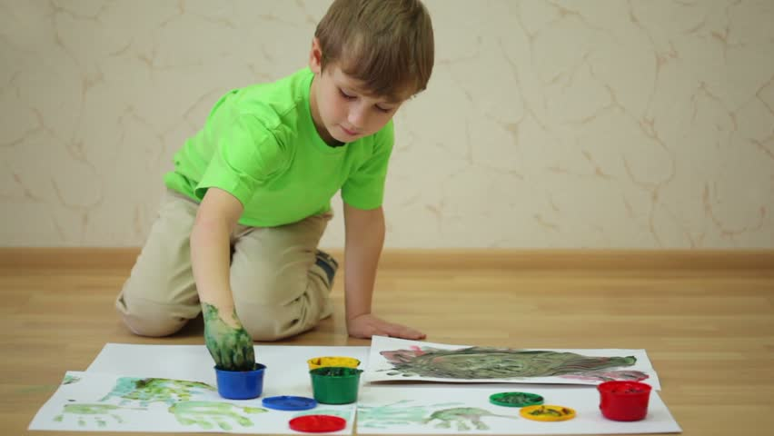 Boy in green t-shirt draws color paints and makes handprints on sheet of white paper