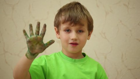 Boy in green T-shirt waves his right palm smeared with coloured paints
