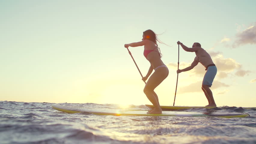 Slow Motion Silhouette Happy Couple Stand Up Paddling Boarding In Ocean