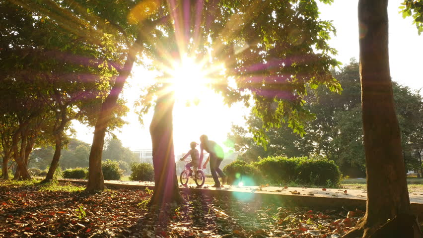 Asian daughter practice to ride a bicycle with her father | Shutterstock HD Video #13625276
