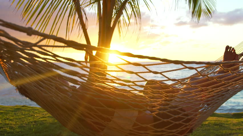 Romantic couple relaxing in tropical hammock at sunset. Summer Luxury Vacation. SLOW MOTION.
