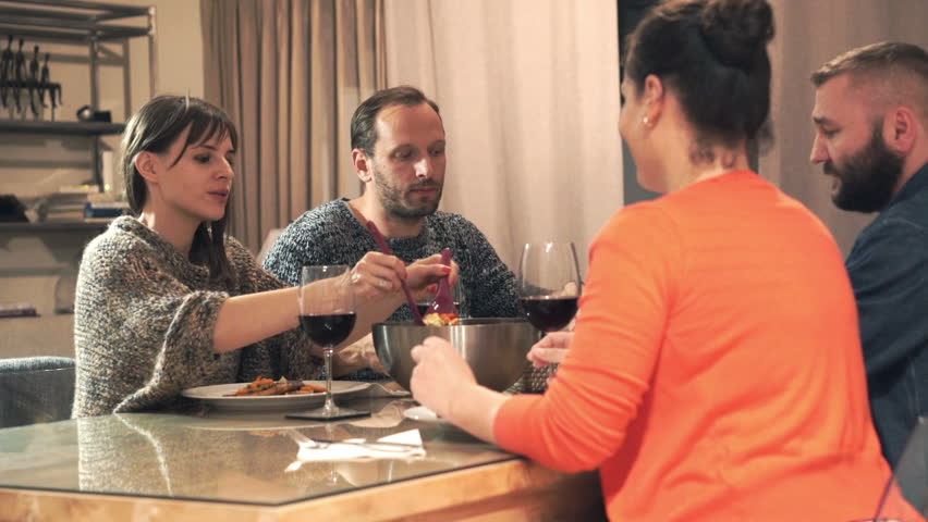 Group of friends talking during dinner at home