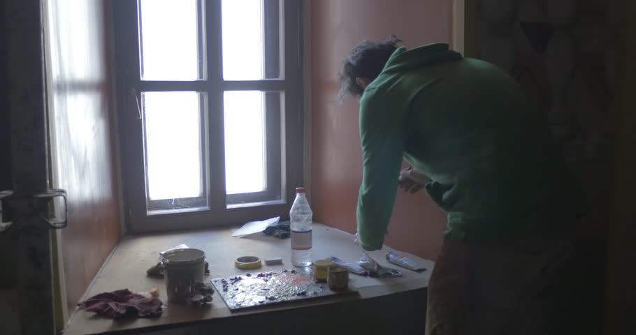 KIEV/UKRAINE - JUL 14 2015: Man, artist in green clothes is standing close to window at windowsill is preparing the paints for painting, indoors #13648952