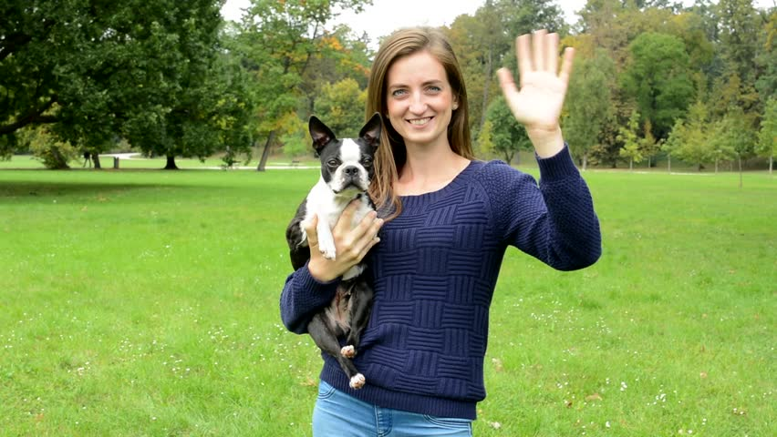 Young attractive woman hug her french bulldog and wave to the camera - eye contact
