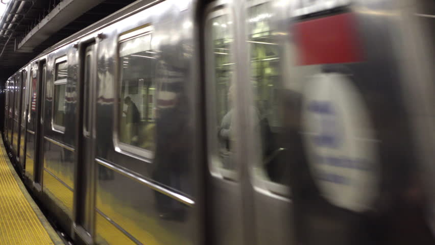 NEW YORK - DEC 7, 2015: 6 train pulling into Astor Place and 8th street NYU station platform in 4K with audio, in NY. MTA provides a rapid transit system for the 5 boroughs.