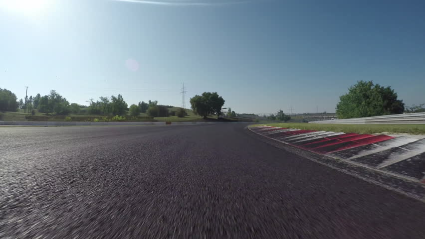 LOW ANGLE VIEW: Race car competing and driving fast on race track lap
