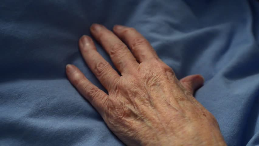 Close up of hand of frail senior being touched in a reassuring manner by mature woman's hand