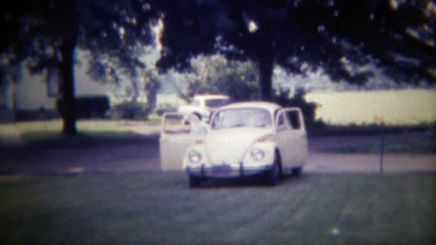 DES MOINES, IOWA 1971: Family arrives in Volkswagen Beetle Bug car parks on lawn.