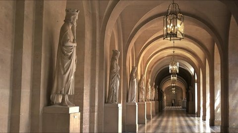 VERSAILLES, PARIS, FRANCE- SEPTEMBER 23, 2015: a zoom in shot of a covered walkway with marble statues at the palace of versailles