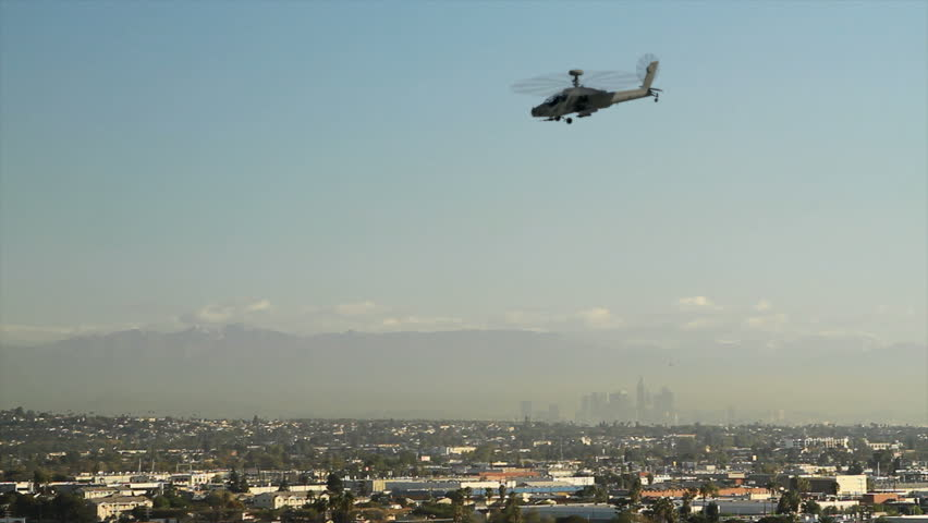 An AH-64 Apache attack helicopter flying over Los Angeles and directly at the camera.   (High quality animation)