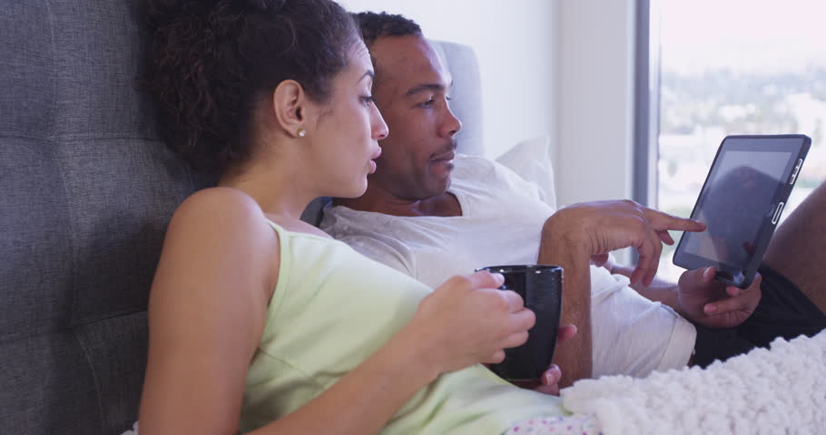 4k Hispanic and Black couple in bed looking at tablet computer sitting in bed Slow motion | Shutterstock HD Video #13716491