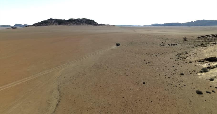Aerial view of a 4x4 car driving through the Namib desert, Namibia