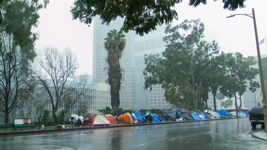 LOS ANGELES, CA, USA  - JANUARY 2016:  Close view of homeless tents lining sidewalk along S Beaudry Avenue next to the 110 freeway in Downtown. Torrents of rain pour down. City skyline in background