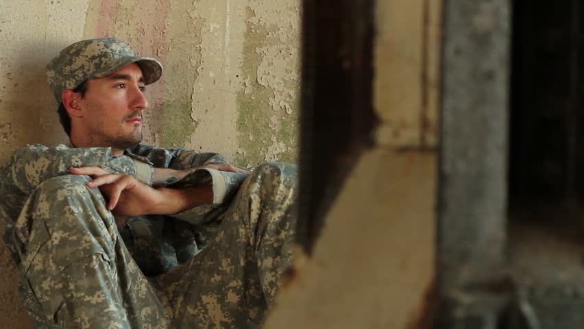 Distraught soldier sitting against concrete wall
