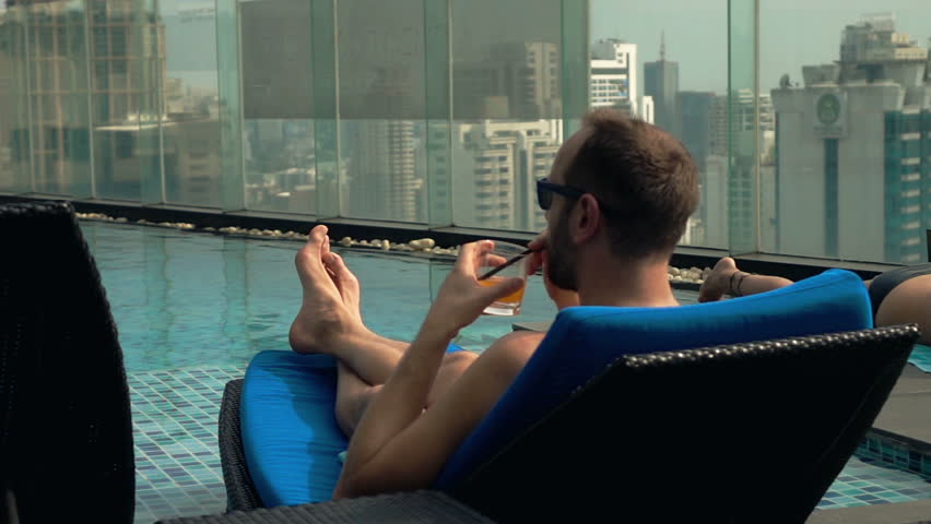 Man relaxing on sunbed drinking cocktail, super slow motion 240fps  | Shutterstock HD Video #13797782