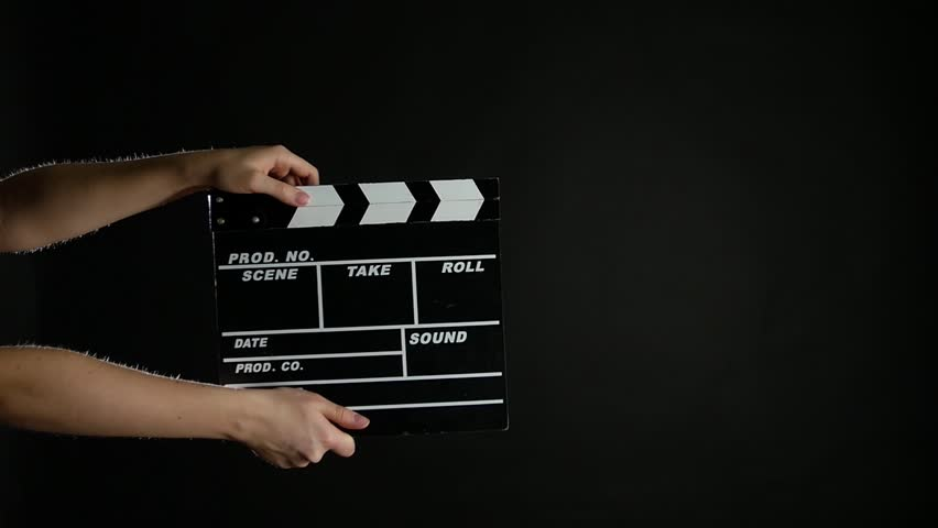 Hands with movie clapper board, on black, slow motion