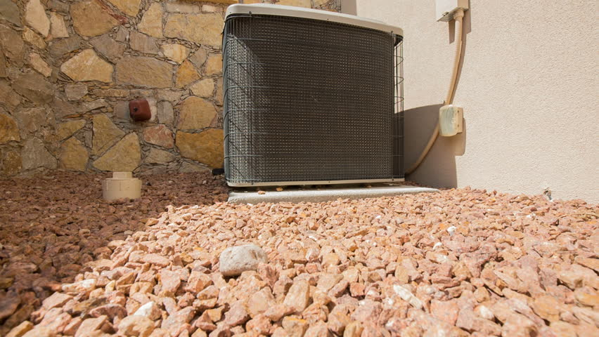 AC Unit Rise and Lower on Stones. camera rises and descends on an air conditioning unit in an arid location. Placed on a stones against a stone and stucco facade