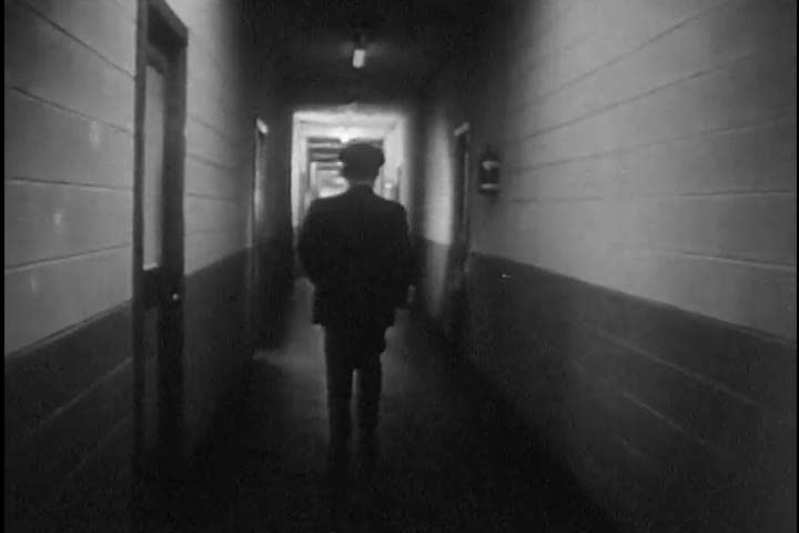 CIRCA 1950s - A security guard walks the hallway with his flashlight at a Zenith facility in the 1950s. | Shutterstock HD Video #13871411