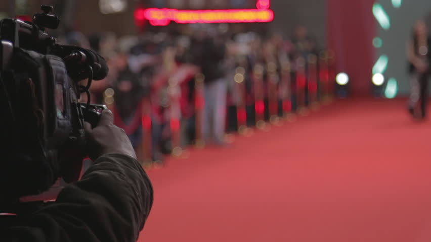 Videographer shoots festive event. A professional cameraman shoots video while passing celebrities on the red carpet. Close up
