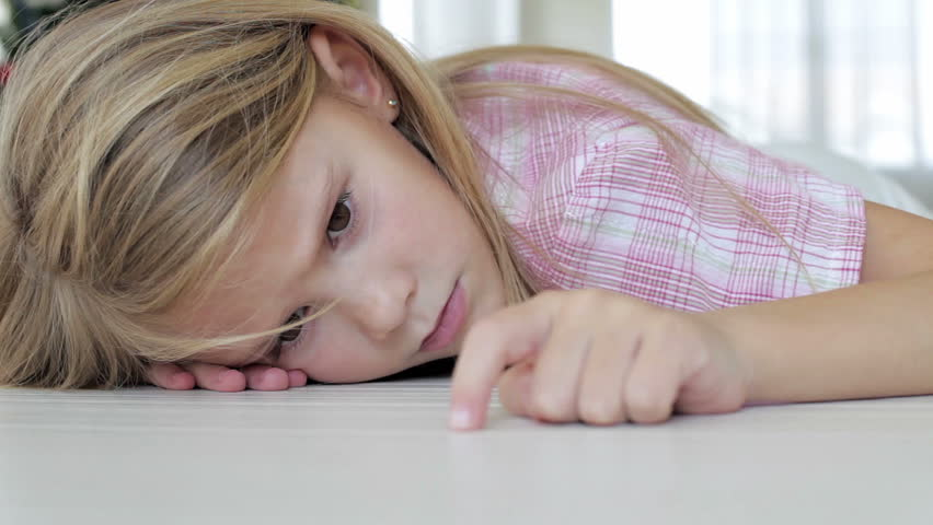 Portrait of sad little girl lying on floor at home at the day time