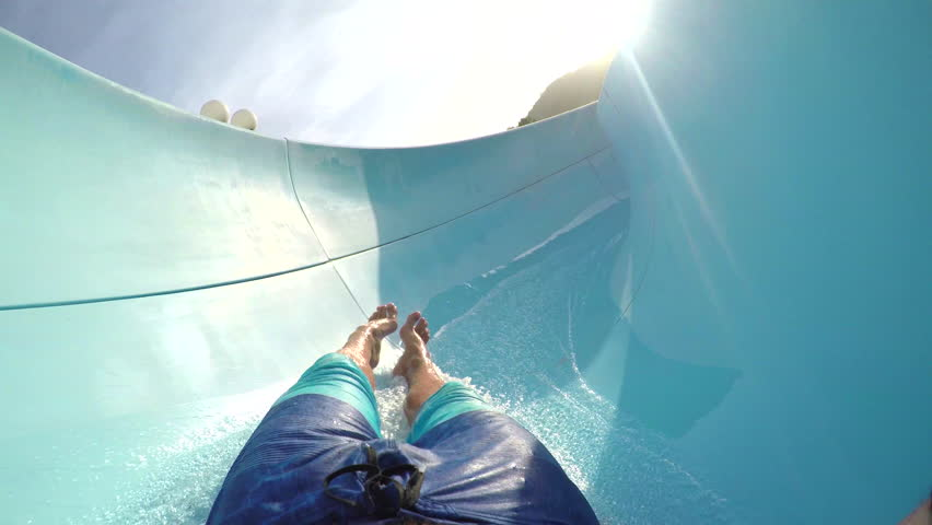 FPV FIRST PERSON VIEW POV: Young adult man sliding down the fun water slide at summer sunset