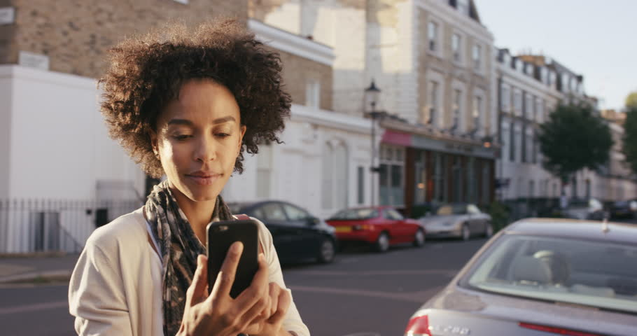 Beautiful Mixed race woman using smart phone technology app walking through city streets living urban happy lifestyle | Shutterstock HD Video #13909196
