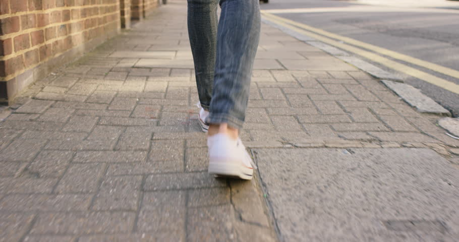 Detail of woman's feet walking through city on pavement from behind