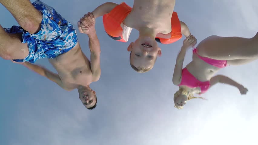 SLOW MOTION CLOSE UP: Young parents and their cute son child jumping over the camera into pool splashing around