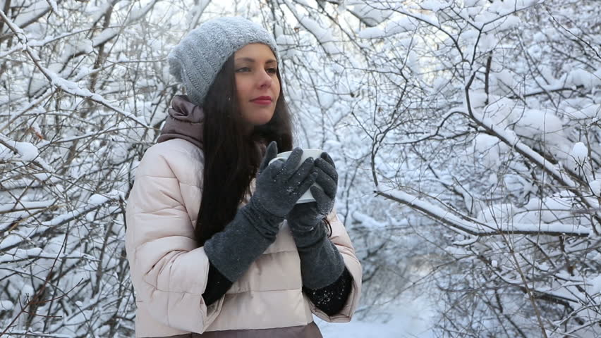 Beautiful happy girl warms up with hot tea. Snow covered trees in winter park. | Shutterstock HD Video #13921493