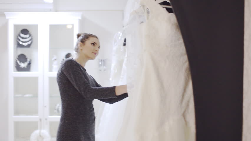 woman chooses wedding gown at bridal boutique #13939010