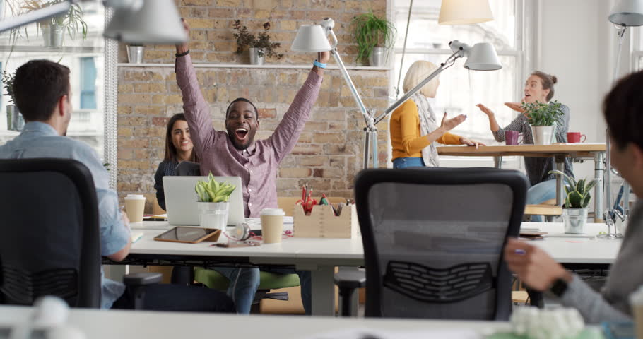 Businessman with arms raised celebrating success watching sport victory on laptop diverse people group clapping expressing excitement in office