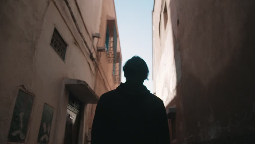 Figure walking through a tight Moroccan alley way  #13949078