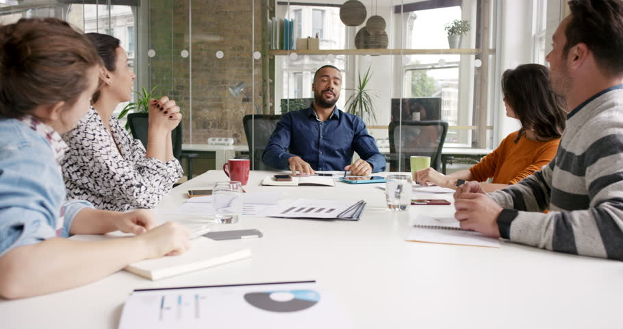 Diverse business people clapping in Creative team meeting celebrating success in casual modern office boardroom with natural light and large open windows | Shutterstock HD Video #13949984