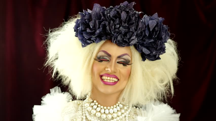 Drag queen with a glamorous and spectacular look acting and talking for camera.