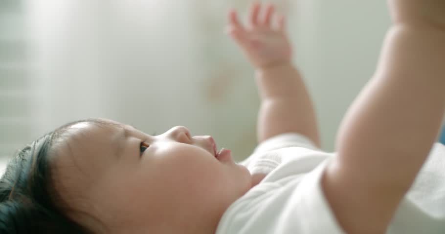 little cute Asian baby drinking from a bottle, extreme close-up, slow motion