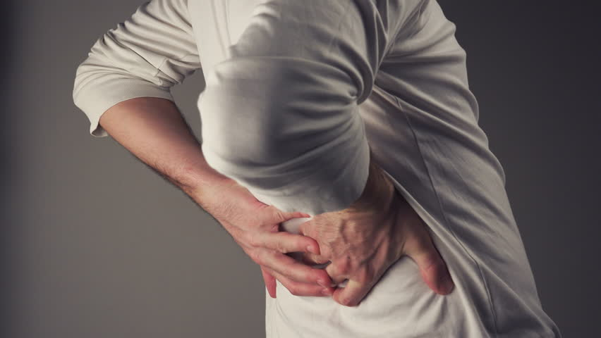 Severe back pain, man suffering from backache having painful cramps.