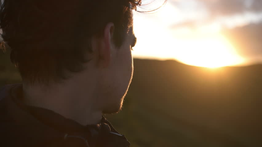 Young caucasian man staring into the sunset on Azores Island, close up shot