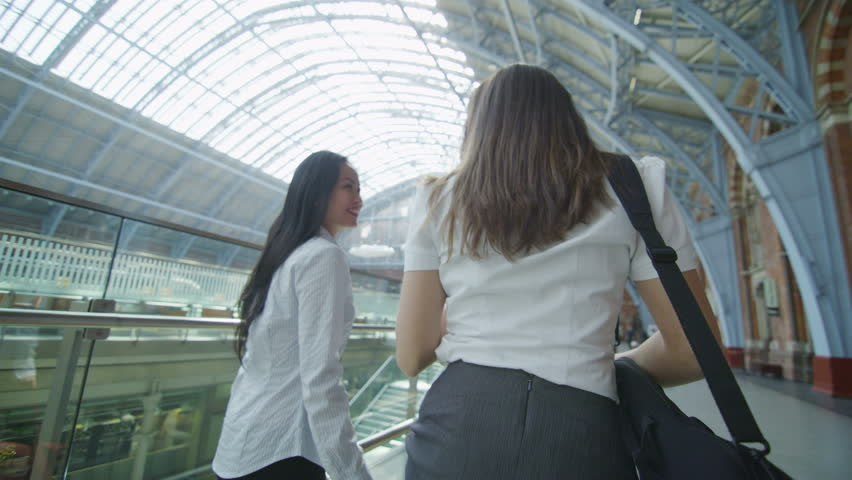 4k / Ultra HD version Attractive female friends or business colleagues chat together as they walk through St. Pancras railway station in London. In slow motion. Shot on RED Epic | Shutterstock HD Video #13999049