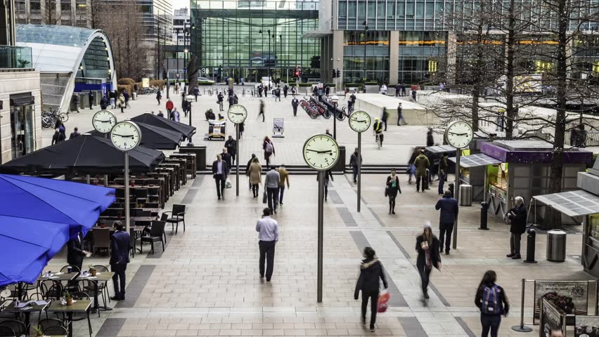 Time lapse view of people rushing from work with several clocks in the docklands financial centre in London