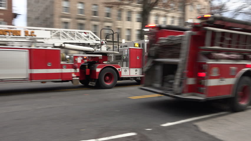 WASHINGTON, DC - JAN. 2016: DC Fire trucks arrive, sirens, one stops lets other turn corner.  Fire truck crews include EMTs, as EMS is part of fire department in DC
