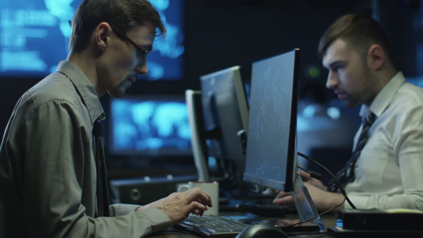 Two IT programmers are working on computers in a dark office room filled with display screens. Shot on RED Cinema Camera in 4K (UHD).