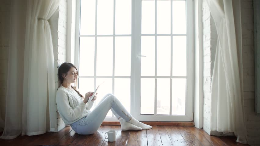 Young woman at home sitting on modern chair in front of window relaxing in her living room using tablet pc #14035640