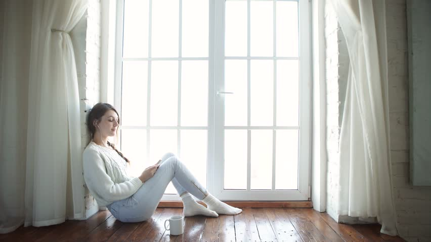 Beautiful young girl sitting at home near a window with a smile looking at phone #14035643