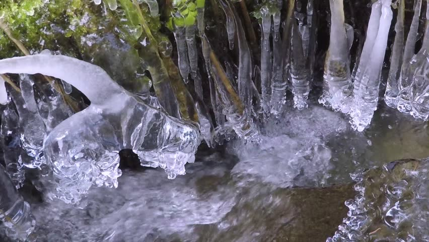 Beautiful frozen stream in the forest with hanging icicles.  | Shutterstock HD Video #14040530