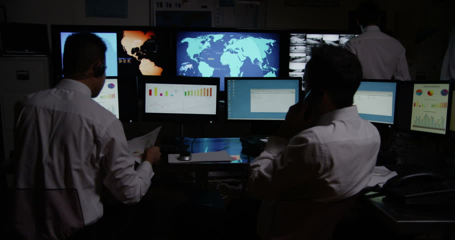 4k / Ultra HD version A team of male security personnel are manning the stations within a busy system control room. It is very dark and the characters are silhouetted against the screens.  #14051006