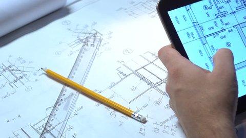 Engineer looking drawings on the tablet.