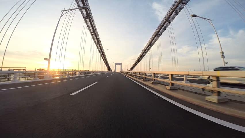 Driver's point of view across the bridge towards the climbing sunshine over the city horizon. Part 2. Tokyo Rainbow Bridge eastbound towards Odaiba. | Shutterstock HD Video #14059463