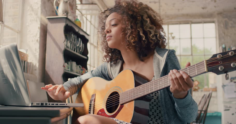 Attractive curly haired mixed race young girl sitting on wooden chair at a window wearing a grey hoodie concentrating focused learning to play guitar using laptop computer at home | Shutterstock HD Video #14075468