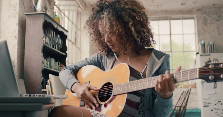 Attractive curly haired mixed race young girl sitting on wooden chair at a window wearing a grey hoodie concentrating focused learning to play guitar using laptop computer at home #14075474